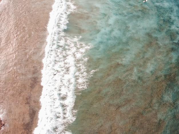Widok z lotu ptaka surferów na falach oceanu atlantyckiego. tło piaszczystej plaży