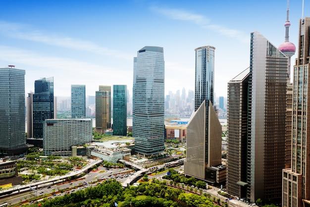 Widok z lotu ptaka szanghaj centralnej dzielnicy biznesowej o wysokiej gęstości. wysokie budynki biurowe i wieżowce ze szklaną powierzchnią. drogi miejskie z wieloma pasami ruchu i zielonym parkiem miejskim. szanghai chiny