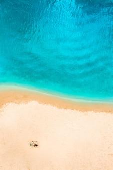 Widok z lotu ptaka top drone pary ludzi na piaszczystej plaży. tło wakacje morze. azure beach woda rzeczna i ludzie.