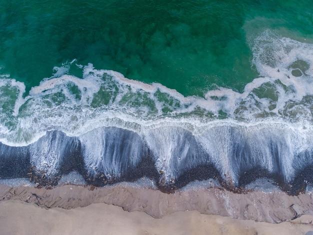 Widok z lotu ptaka turkusowych fal docierających do brzegu
