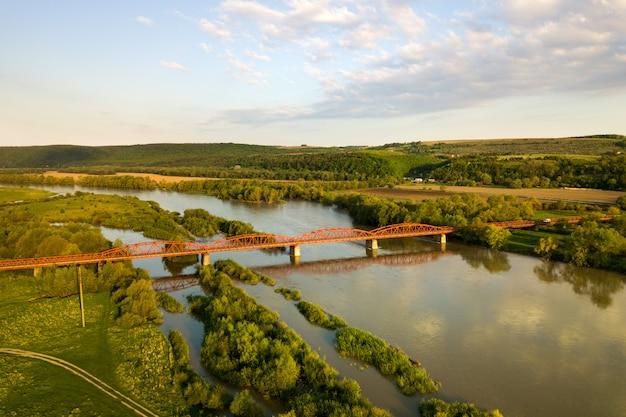 Widok z lotu ptaka wąski drogowy most rozciąga się nad błotnistą szeroką rzeką w zielonym obszarze wiejskim.