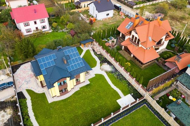 Widok z lotu ptaka wiejskich domów prywatnych z panelami fotowoltaicznymi.