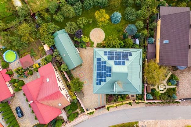 Widok z lotu ptaka wiejskiego prywatnego domu z panelami fotowoltaicznymi do produkcji czystej energii elektrycznej na dachu. autonomiczny dom w koncepcji dzielnicy mieszkalnej.