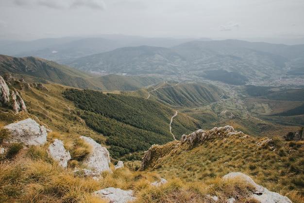 Widok z lotu ptaka wiejskiej drogi przechodzącej przez drzewa i góry