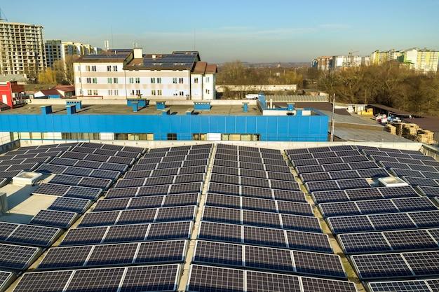 Widok z lotu ptaka wielu fotowoltaicznych paneli słonecznych zamontowanych na dachu budynku przemysłowego.