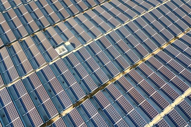 Widok z lotu ptaka wielu fotowoltaicznych paneli słonecznych zamontowanych na dachu budynku przemysłowego