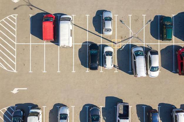 Widok z lotu ptaka wielu kolorowych samochodów zaparkowanych na parkingu z liniami i oznaczeniami miejsc parkingowych i kierunków.