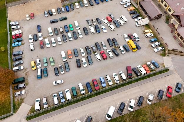 Widok z lotu ptaka wielu kolorowych samochodów zaparkowanych na publicznym parkingu.
