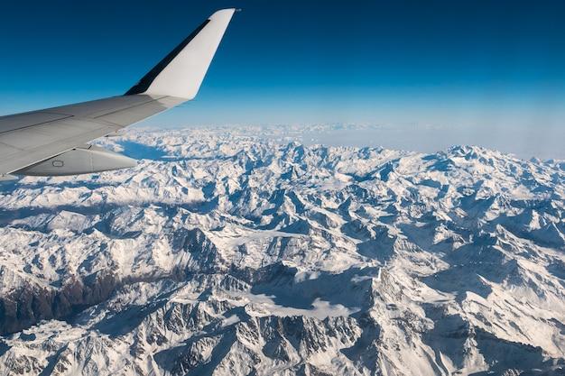 Widok z lotu ptaka włoskich szwajcarskich alp w zimie, z ogólnym skrzydłem samolotu.