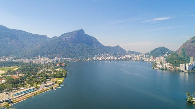 Widok z lotu ptaka wody morskiej jeziora rodrigo de freitas lagoon (lagoa) w mieście rio de janeiro. w tle widać posąg chrystusa odkupiciela.