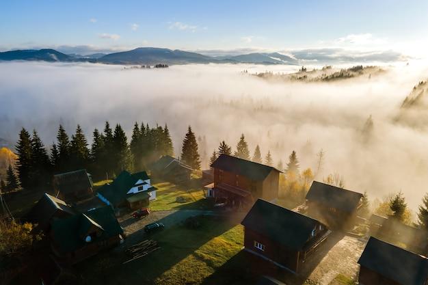 Widok z lotu ptaka wsi domy na szczycie wzgórza w górach jesienią mglisty o wschodzie słońca.