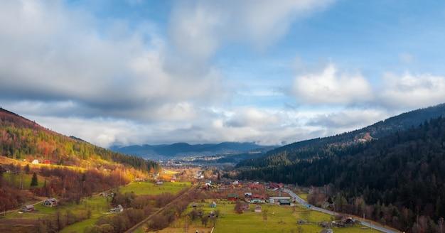Widok z lotu ptaka wsi wiejskiej między górskimi wzgórzami porośniętymi lasem sosnowym. naturalny krajobraz.