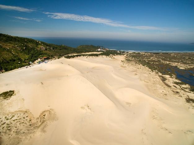 Widok z lotu ptaka wydmy w słoneczny dzień - plaża joaquina - florianopolis - santa catarina - brazylia.