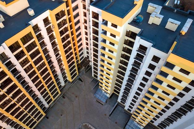 Widok z lotu ptaka wysoki kompleks budynków mieszkaniowych. niebieski płaski dach z kominami, wewnętrzny dziedziniec, rząd okien. fotografia dronów.