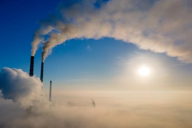 Widok z lotu ptaka wysokich rur elektrowni węglowej z czarnym dymem poruszającym się w górę zanieczyszczającej atmosfery o wschodzie słońca.