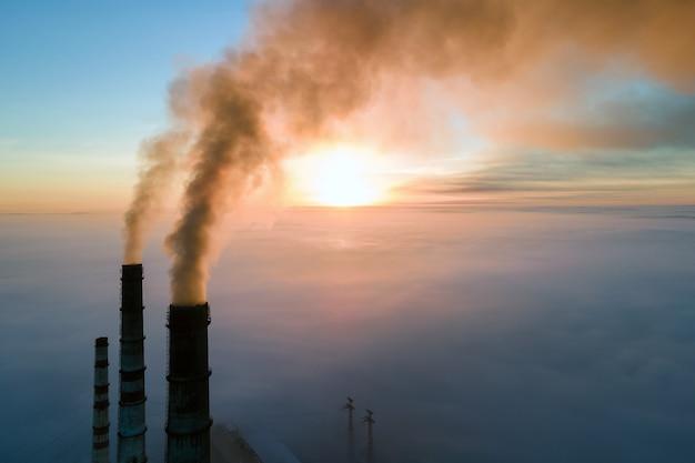 Widok z lotu ptaka wysokich rur elektrowni węglowej z czarnym dymem poruszającym się w górę zanieczyszczającej atmosfery o zachodzie słońca.