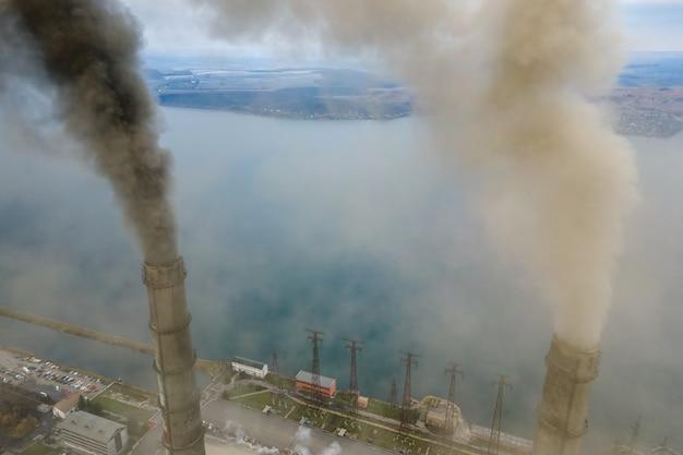 Widok z lotu ptaka wysokich rur elektrowni węglowej z czarnym dymem w górę zanieczyszczającej atmosfery.