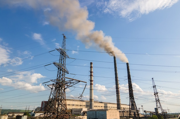 Widok z lotu ptaka wysokich rur elektrowni węglowej z czarnym kominem zanieczyszczającym atmosferę. produkcja energii elektrycznej z koncepcją paliw kopalnych.