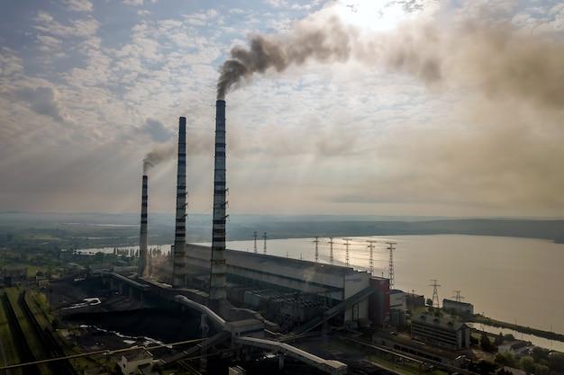 Widok z lotu ptaka wysokich rur kominowych z szarym dymem z elektrowni węglowej.