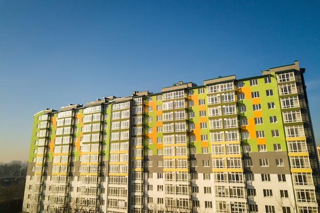 Widok z lotu ptaka wysokiego budynku mieszkalnego z wieloma oknami i balkonami.