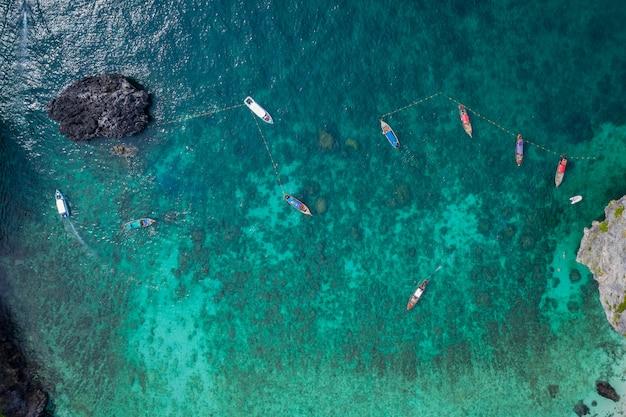 Widok z lotu ptaka wyspy phi phi w sezonie tajskim i zagranicznym turyści snurkują wypożyczając łódkę z długim ogonem i łódkę do podróży