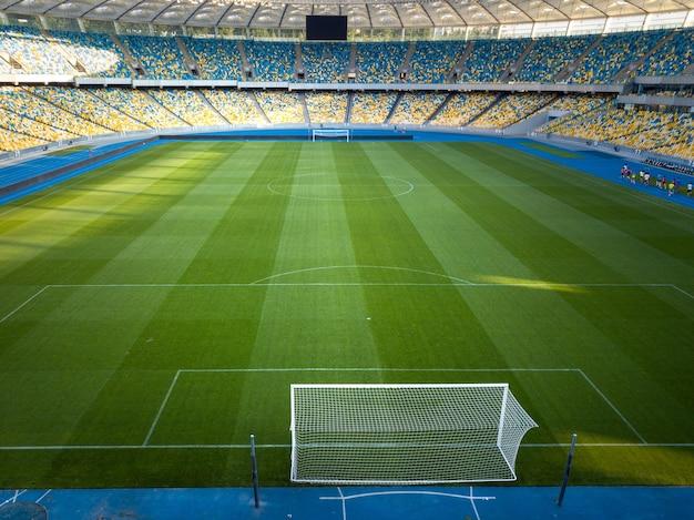 Widok z lotu ptaka z drona bramy piłkarskie na zielonym stadionie z żółto-niebieskimi trybunami olimpijskiego narodowego kompleksu sportowego.