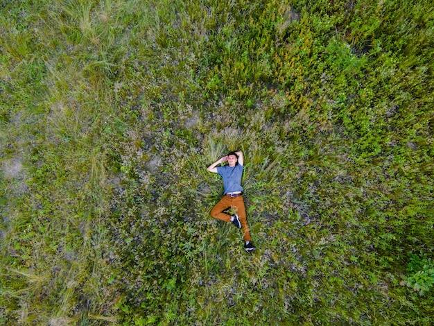 Widok z lotu ptaka z drona mężczyzny w wysokiej trawie