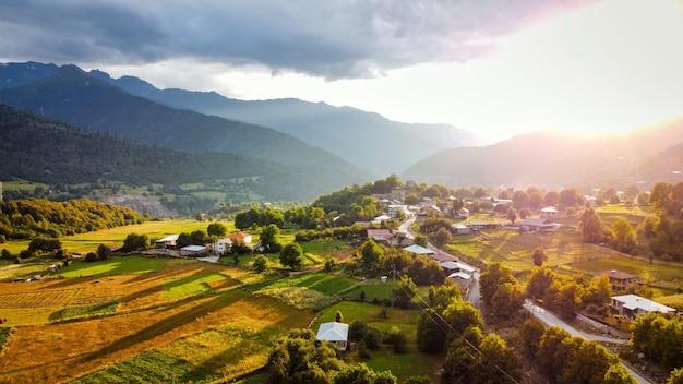 Widok z lotu ptaka z drona na wieś w gruzji o zachodzie słońca doliny pól i budynków gór i wzgórz
