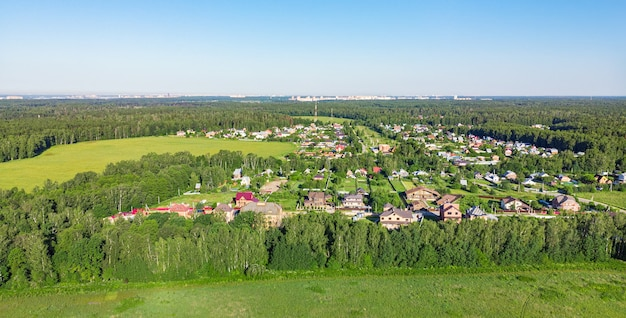 Widok z lotu ptaka z drona wiejskiej wioski, pól i lasów dookoła