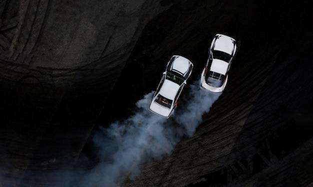 Widok z lotu ptaka z góry dwa samochody dryfujące bitwy na asfaltowym torze wyścigowym z dużą ilością dymu.