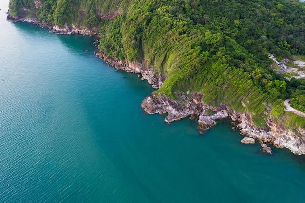 Widok z lotu ptaka z góry fal oceanu, plaży i skaliste wybrzeże i piękny las.