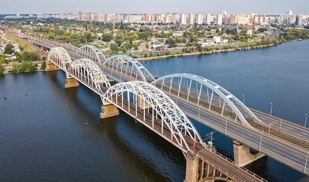 Widok z lotu ptaka z góry mostu samochodowego i kolejowego darnitsky przez dniepr
