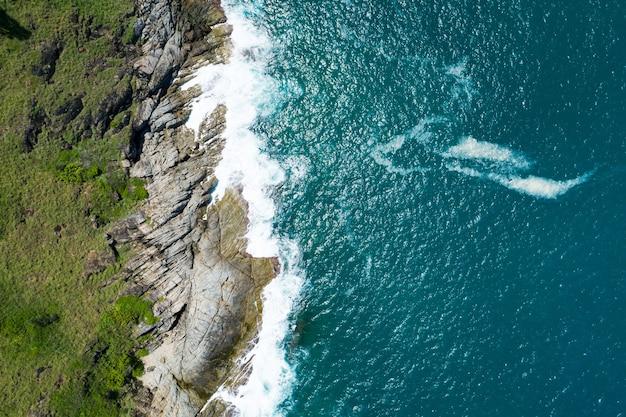 Widok z lotu ptaka z góry na dół fala wybrzeża rozbija się na brzegu morza piękna turkusowa powierzchnia morza w słoneczny dzień dobra pogoda dzień lato w tle niesamowity widok z góry na morze.