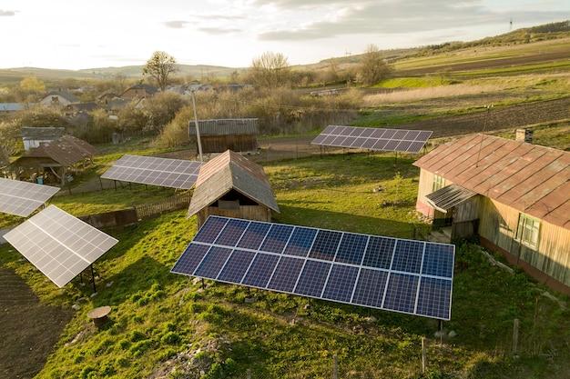 Widok z lotu ptaka z góry na panele słoneczne w zielonym wiejskim podwórku.