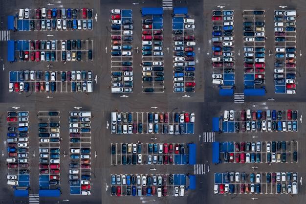 Widok z lotu ptaka z góry parking z wieloma samochodami. wiele samochodów jest zaparkowanych na parkingu z białymi oznaczeniami. miejsca parkingowe ze wzorem pojazdów.