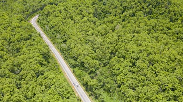 Widok z lotu ptaka z góry samochód jadący przez las na wiejskiej drodze, widok z drona