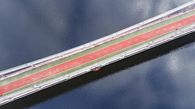 Widok z lotu ptaka z góry ścieżki dla pieszych i rowerzystów na moście park w zimie i dniepr z góry, miasto kijów (kijów), ukraina
