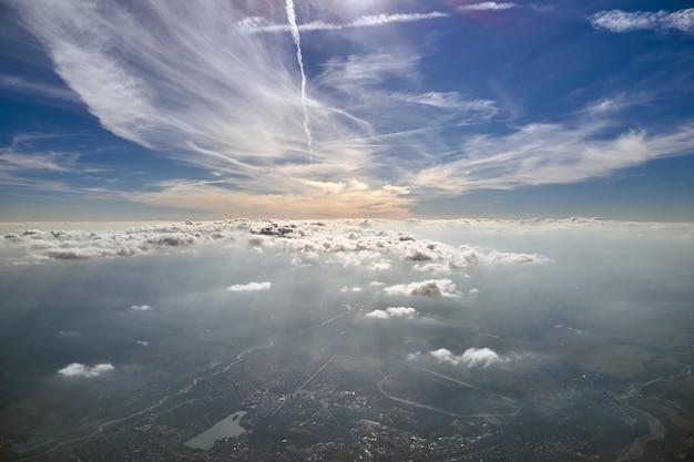 Widok z lotu ptaka z okna samolotu na dużej wysokości odległego miasta pokrytego warstwą cienkiego mglistego smogu i odległych chmur.