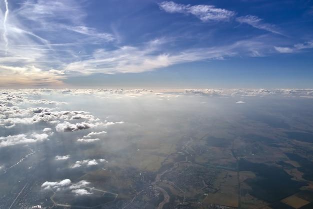 Widok z lotu ptaka z okna samolotu na dużej wysokości ziemi pokrytej białą cienką warstwą mglistej mgły i odległych chmur.