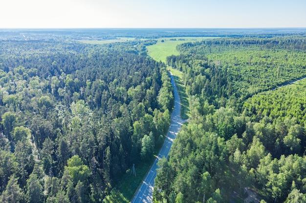 Widok z lotu ptaka z zielonego lasu. droga w lesie z góry.