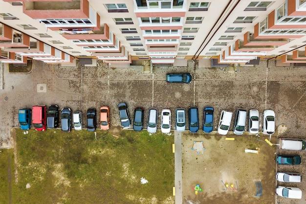 Widok z lotu ptaka zaparkowanych samochodów na parkingu między wysokimi apartamentowcami.