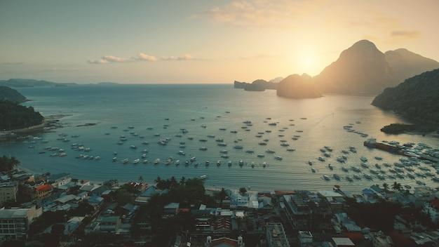 Widok z lotu ptaka zatoki oceanu na zachód słońca w porcie z transportu wodnego w tropikalnym pejzażu. rajskie miasto