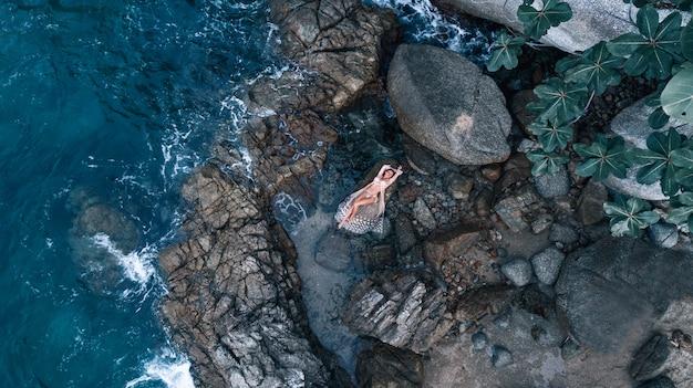Widok z lotu ptaka: zdjęcie pięknej, pozującej dziewczyny leżącej w białej sukni, wśród skał blisko morza.