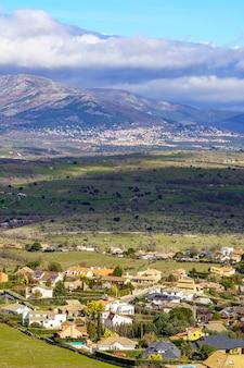 Widok z lotu ptaka zielony górski krajobraz z ciemnymi chmurami i wioskami z domami na zboczu góry. navacerrada madrid. europa.