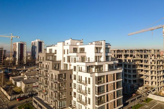 Widok z lotu ptaka żurawia wieżowego i budynków mieszkalnych w budowie. rozwój nieruchomości.