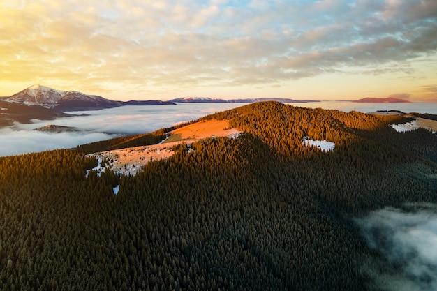 Widok z lotu ptaka żywy wschód słońca nad górskimi wzgórzami pokrytymi wiecznie zielonym lasem świerkowym jesienią.