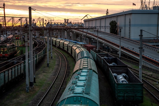 Widok z mostu kolejowego na pociągi towarowe o zachodzie słońca.