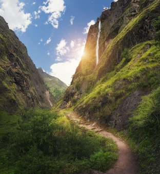 Widok z niesamowitymi himalajami pokrytymi zieloną trawą, wysokim wodospadem, piękną ścieżką, zielonymi drzewami, błękitnym niebem ze słońcem i chmurami w nepalu o zachodzie słońca. kanion górski. podróżuj po himalajach.krajobraz