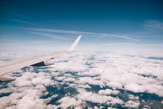 Widok z okna samolotu na chmury i skrzydło