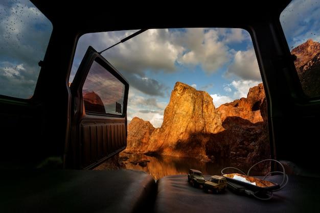 Widok z otwartego bagażnika samochodu na szczycie góry i jeziora.